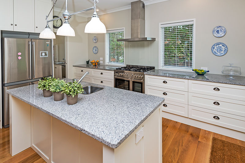 Beautiful traditional kitchen cabinets, granite benchtop and feature lights in award winning home