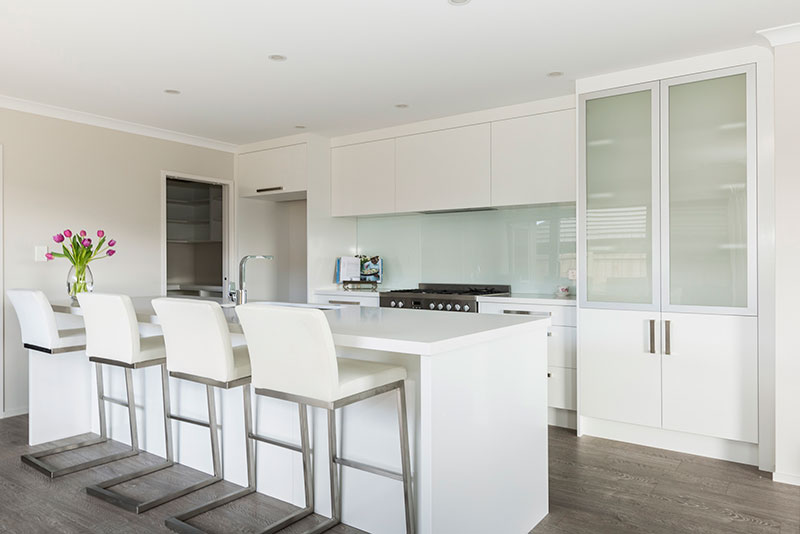 Simple White kitchen with island bench, cut glass coloured splashback and timber floor