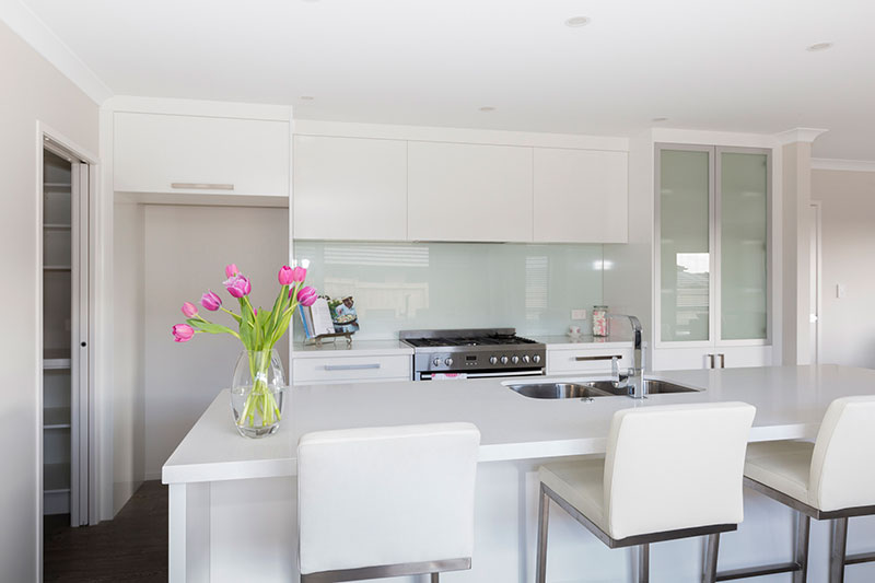 Beautiful light white kitchen with island bench. white barstools and vase of pink tulips