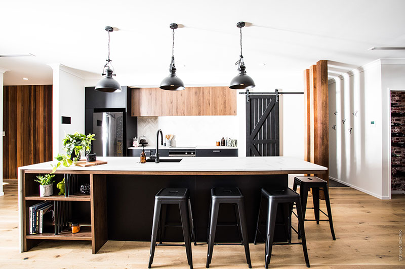 Black and wood kitchen with black industrial pendents, barn door and under bench shelves