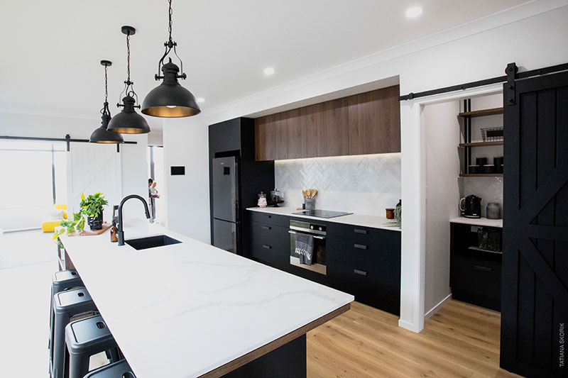 White bench top and black cabinets in showhome kitchen at Paerata Rise. Black barn door & scullery with suspended shelves