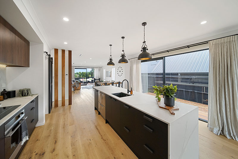 Black kitchen cabintery with white marble benchtop, cedar posts, timber floor and black pendent lights